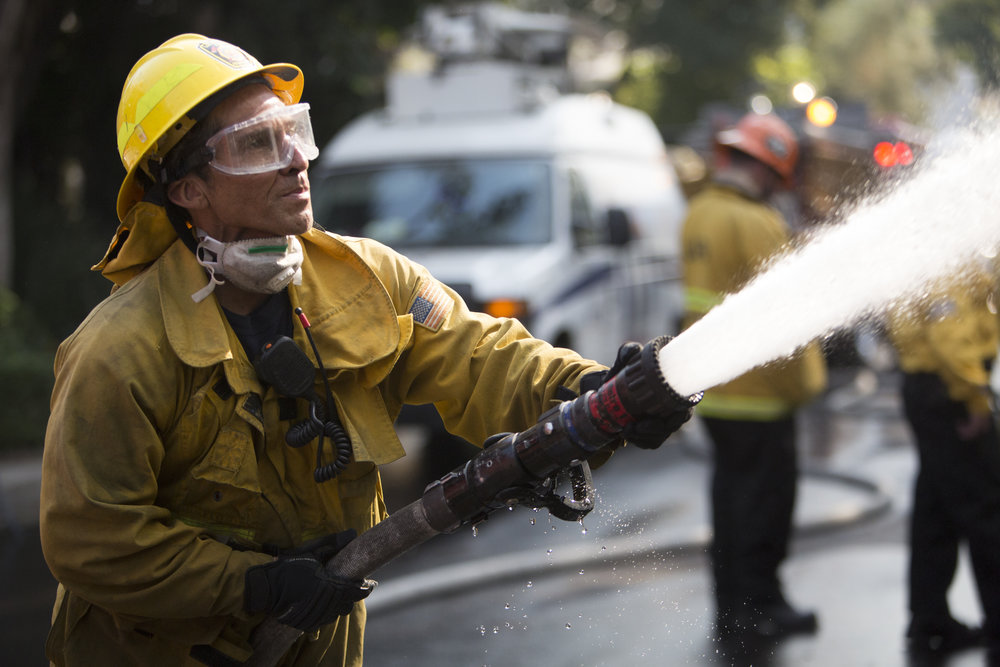 Los Angeles Fire Department engine company 71, firefighter Luis Vargas, works to put out the flames of a burning house at The Skirball Fire, which shut down the 405 north and burned 450 acres of land. On Dec.6, 2017 in West Los Angeles, Calif. (Photo by Daniel Bowyer)