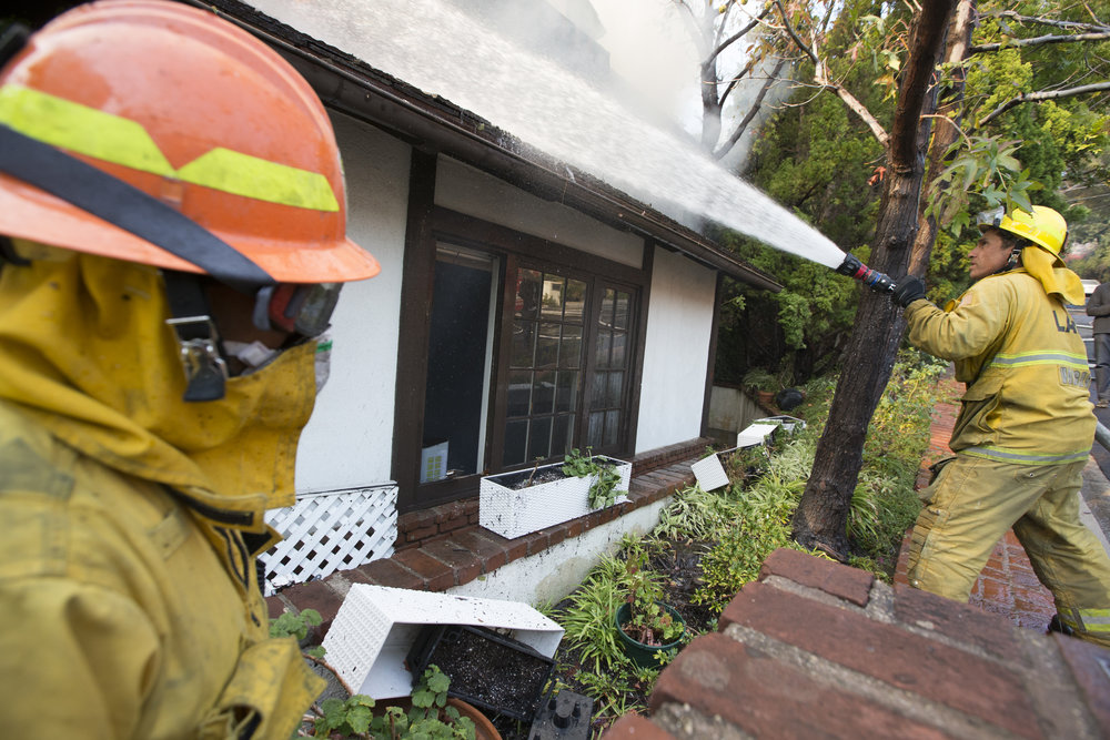 Los Angeles Fire Department engine company 71, firefighter readies a hose to put out the flame. The Skirball Fire, which shut down the 405 and burned 450 acres of land on Dec.6, 2017 in West Los Angeles, Calif. (Photo by Daniel Bowyer)