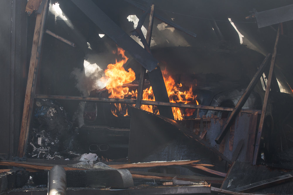 A car burns in the garage port of a home on Casiano Road that was hit by the Skirball Fire on Wednesday, Dec.6, 2017 in the Bel-Air area of Los Angeles, Calif. (Jose Lopez)