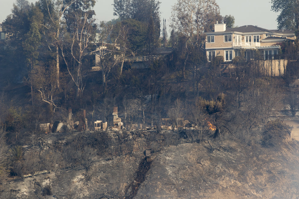 Flames remain visible in one of the homes that burned down during the Skirball fire on Wednesday, December 6, 2017 in the Bel-Air area of Los Angeles, California. (Jose Lopez)