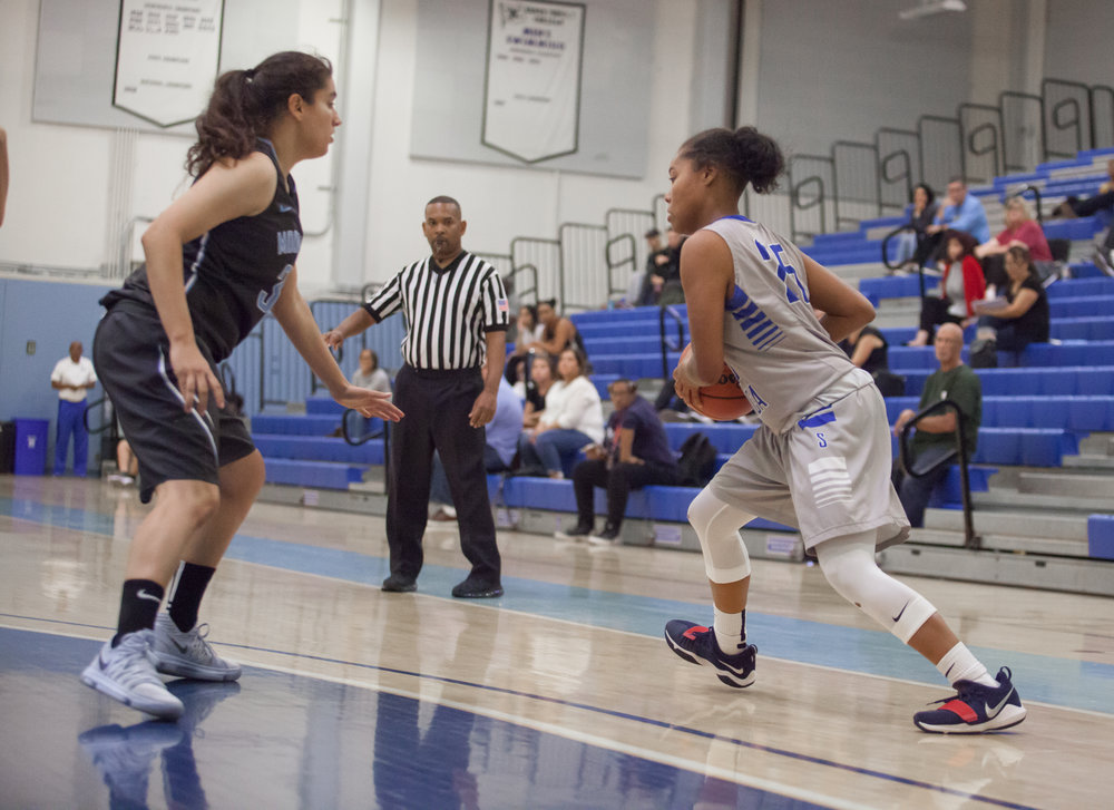 Mija Williams (25) of the Santa Monica College looks for an opening to create a shot while being defended by guard Hannah Sharifi (3) of the Moonpark College. The Santa Monica College Corsairs loss the home game 52-69 against the Moonpark College. The game held on Saturday, December 9th, 2017 at Santa Monica College Pavilion at Santa Monica College Main Campus in Santa Monica, California. (Photo by Elena Rybina)