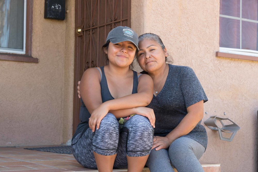 "Santa Monica College student and DACA recipient and activist Salma Morales Aguilar pictured with her mother, Brigida Morales Aguilar, in Los Angeles, Calif. on Saturday, October 21, 2017. They are pictured sitting on the steps of one of the first homes they lived in when they first came to Los Angeles from Mexico. ""We moved around a lot when I was little,"" says Salma Aguilar Morales. (Photo by Helena Sung)."