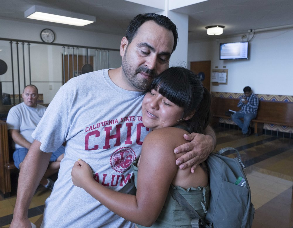 "Santa Monica College student and activist, Salma Aguilar Morales, 19, receives a hug from Oscar de la Torre, Executive Director of the Pico Youth & Family Center and member of the Santa Monica Malibu Unified School District, after speaking at a rally at Santa Monica City Hall in Santa Monica, Calif. on September 7, 2017. A DACA recipient, Aguilar Morales was 10 months old when her parents brought her to California from Oaxaca, Mexico. ""It's really about politics, and that's what we need to learn,"" says Aguilar Morales of the undocumented immigrant community. (Photo: Helena Sung)"