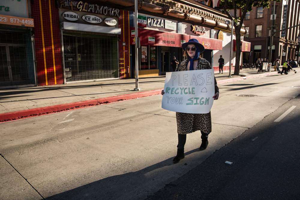 A marcher reminds other demonstrators to recycle their signs at the second Women's March on Washington in Los Angeles, Calif. on Jan 20, 2018. An estimated 600,000 supporters of various human rights issues began the march at Pershing Square in downtown Los Angeles and gathered at the destination where guest speakers and live musical performances were hosted on a stage in front of the Los Angeles City Hall steps. Hollywood celebrities representing the #TimesUp movement such as Natalie Portman and Scarlet Johansson spoke about their experiences with sexual harassment and called for attendees to end workplace harassment and assault for women in working class jobs. When asked if the movement has plans to mobilize supporters throughout the rest of the year, Deena Katz, Co-Executive Director of Women's March Los Angeles Foundation, said their focus for 2018 would be voter education and voter registration. Photographer/Zin Chiang.