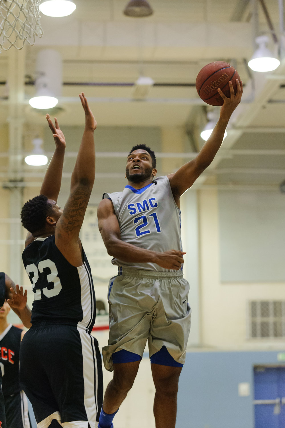 Forward Khalil Taylor (21,Right) of Santa Monica College goes up for a left-handed layup on a contest by Rashaad Johnson (23,Left) of Pierce College. The Santa Monica Corsairs lose their final game of the season 103-91 to the Pierce College Brahmas. The game was held at the SMC Pavilion at the Santa Monica College Main Campus in Santa Monica, Calif.. February 17, 2018. (Photo by: Justin Han/Corsair Staff)
