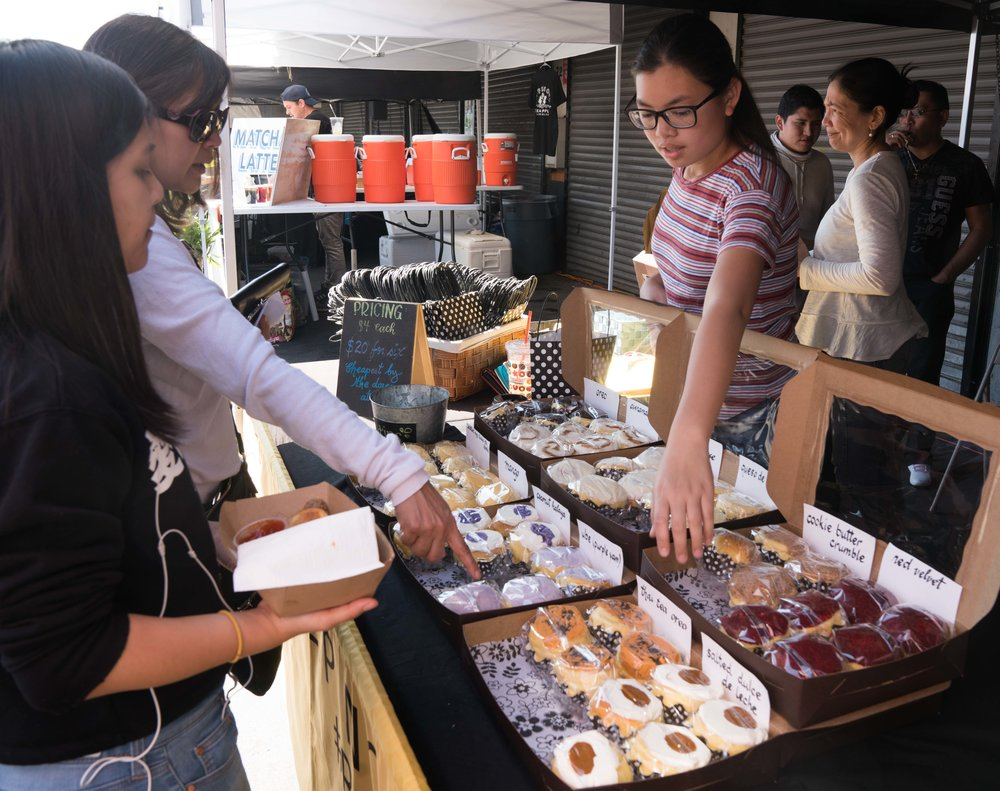 Natalie Reyes, 13, (on right) helps customers pick out different flavors of Filipino brioche buns at Smorgasburg LA in the downtown section of Los Angeles, Calif. Reyes' mother, Chari Reyes, is the owner of Ensaymada Project, a home-based business making Filipino brioche buns. (Photo by Helena Sung)