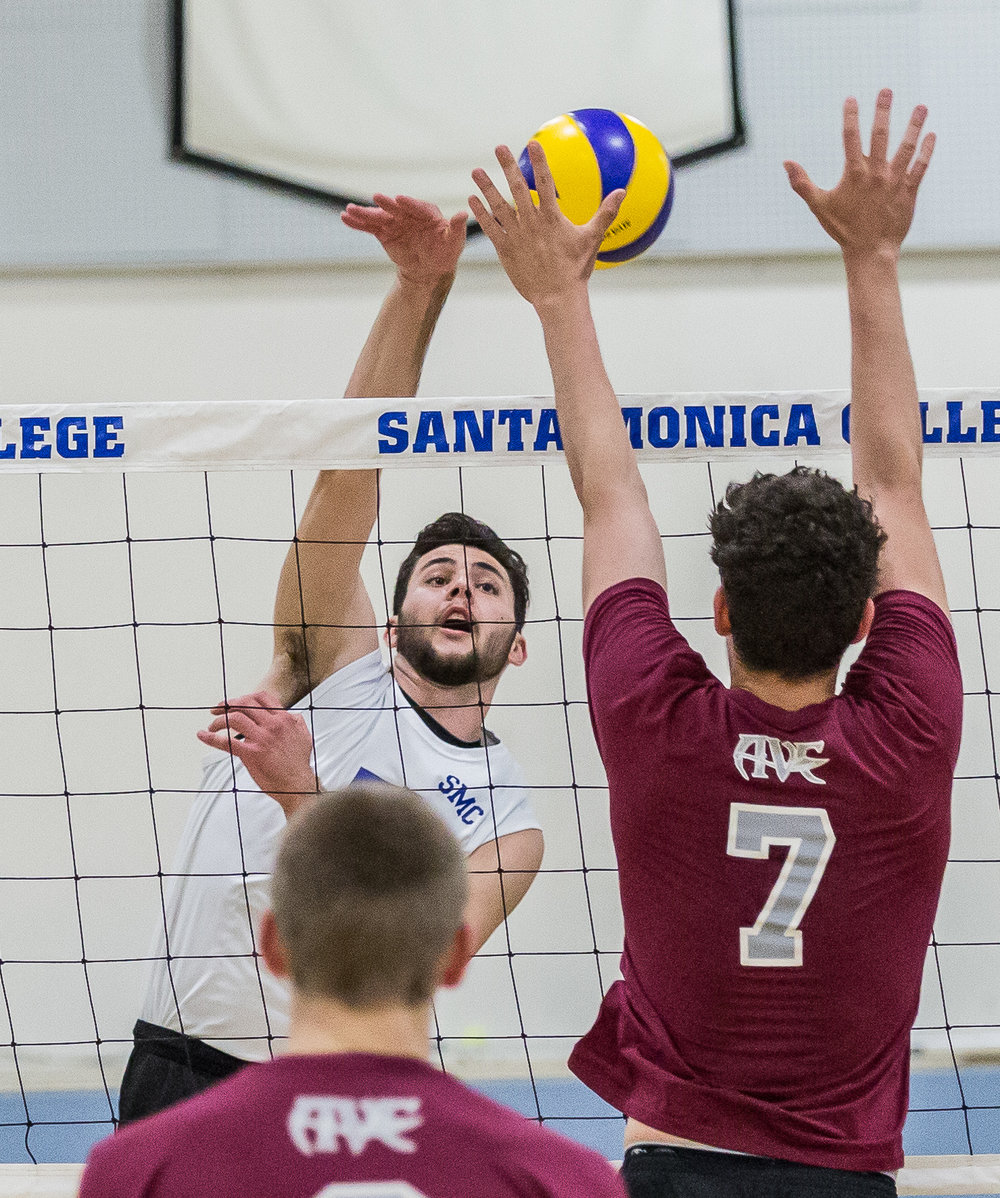 Santa Monica College Corsair right-side hitter Andrew Dalmada #5 (center, white) attempts to spike the ball, as the defending Antelope Valley College Marauder opposite hitter Kevin Moore #7 (right, red) tries to block said spike during the Corsairs 3-0 blowout victory against the Marauders in the Santa Monica College (SMC) Pavilion at the SMC main campus in Santa Monica Calif., on Friday, March 2, 2018 (Corsair Photo: Matthew Martin)