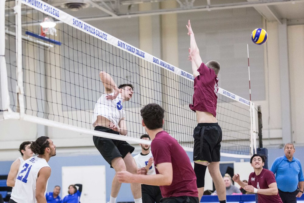 Santa Monica College Corsair middle-hitter Nick Kostetsky #8 (center, white) spikes the ball through the Antelope Valley College Marauder' defense during the Corsairs 3-0 blowout victory against the marauders in the Santa Monica College (SMC) Pavilion at the SMC main campus in Santa Monica Calif., on Friday, March 2, 2018 (Corsair Photo: Matthew Martin)