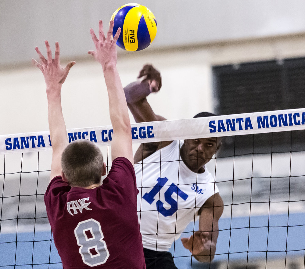 The Santa Monica College Corsair middle hitter Vecas Lewin #15 (center-right, white) nails a powerful spike through the defending Antelope Valley College Marauder middle blocker Matthew Lee #8 (center-left, red) during the Corsairs 3-0 blowout victory against the Marauders in the Santa Monica College (SMC) Pavilion at the SMC main campus in Santa Monica Calif., on Friday, March 2, 2018 (Corsair Photo: Matthew Martin)