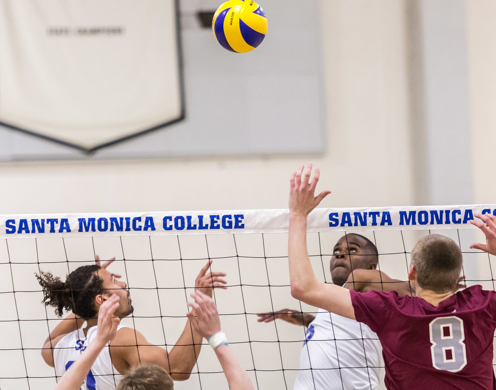 Santa Monica College (SMC) Corsair setter Hunter Dougles #21 (left, white) sets the ball up for SMC Corsair middle-hitter Vecas Lewin #15 (right, white) to spike the ball into the Antelope Valley College Marauder's defense during the Corsairs 3-0 blowout victory against the marauders in the Santa Monica College (SMC) Pavilion at the SMC main campus in Santa Monica Calif., on Friday, March 2, 2018 (Corsair Photo: Matthew Martin)
