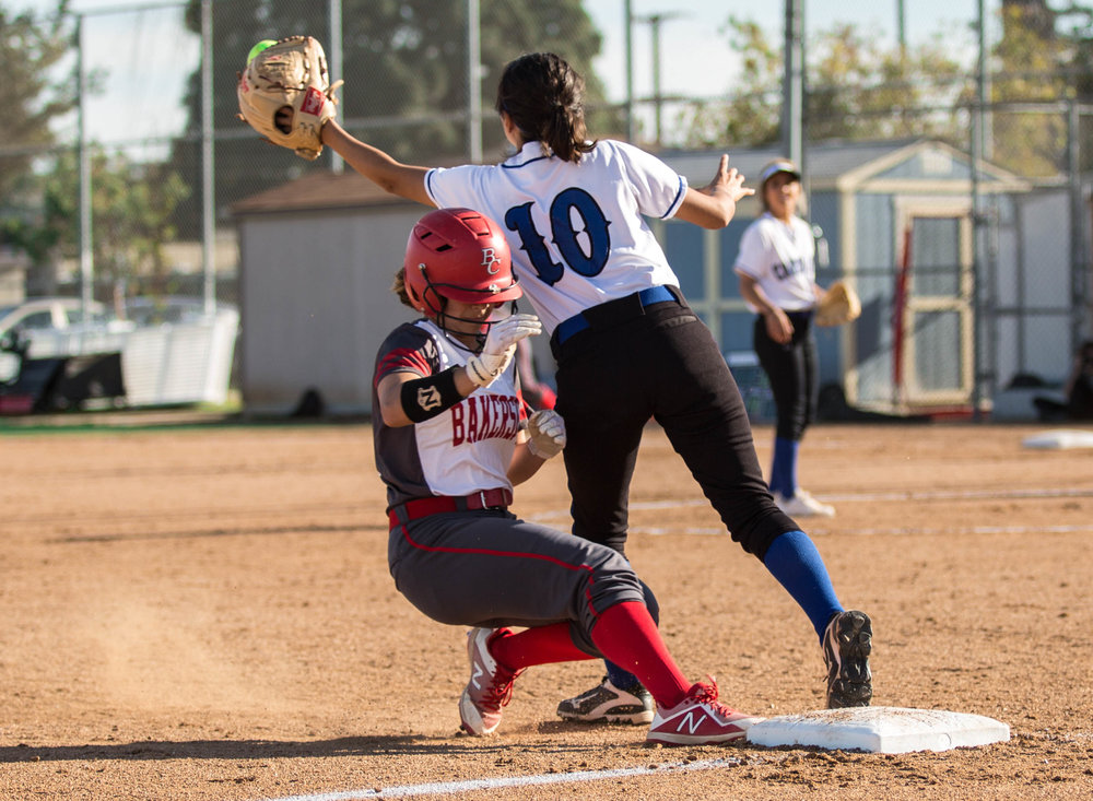 Bakersfield College Renegade freshman infielder/outfielder Ashley Hernandez #1 (left, red) slides into first third base as Santa Monica College Corsair freshman infielder Briana Osuna #10 (right, white) unsuccessfully tries to tag Hernandez during the bottom of the 6th at the Santa Monica College Corsair Field in Santa Monica California, on Tuesday, March 6, 2018. The Corsairs would go on to lose the game to Bakersfield College 0 – 9, making their tally for the season 6 wins and 11 losses. (Corsair Photo: Matthew Martin)