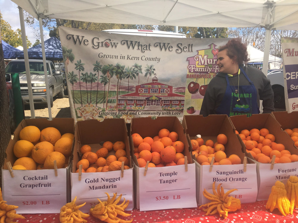 A wide selection of unusual, exotic citrus fruits with welcoming employee Jazz Bodi in the background, sold by Murray Family Farm at the Saturday farmers market in Santa Monica, Calif. on March 3, 2018. (Photo by: Claudia Vardoni)