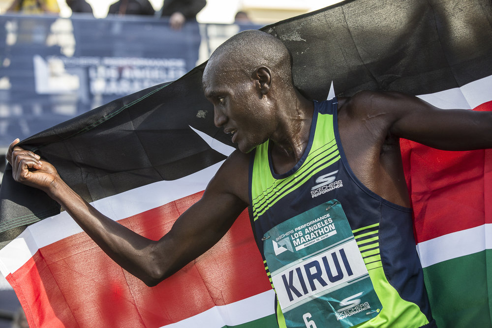 Weldon Kirui proudly holds the flag of his native country Kenya over himself after winning the 33rd annual Los Angeles Marathon on March 18, 2018 in Santa Monica, California with a time of 2:11:48. Kirui has won 2 out of the last 3 Los Angeles Marathons. (Matthew Martin/Corsair Photo)