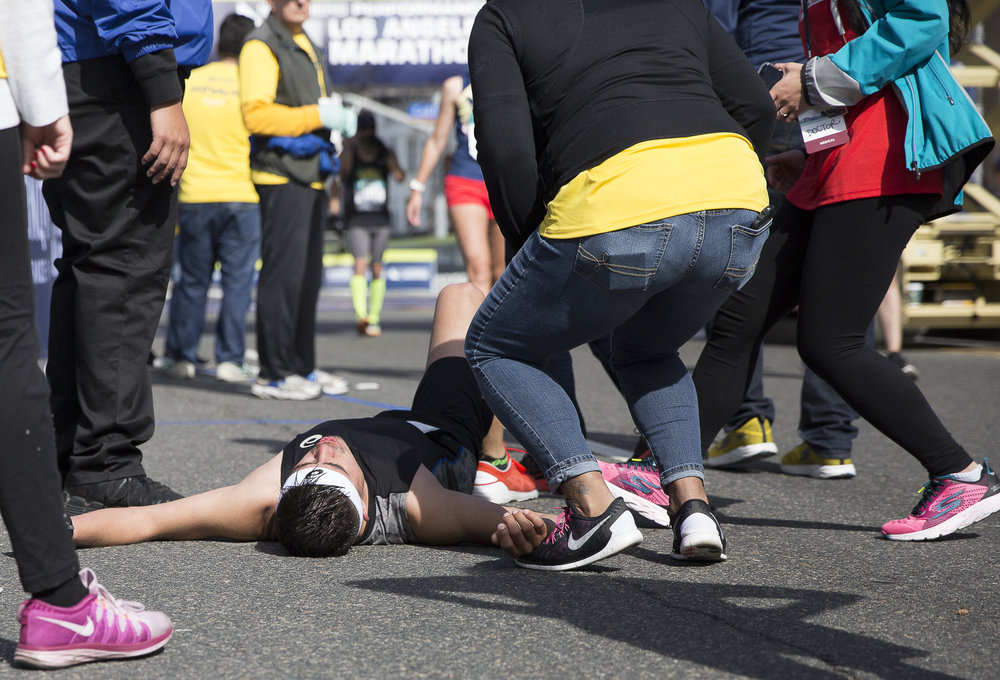 "Los Angeles Marathon participant Devon Cox collapses and is rushed by volunteer ""hotwalkers"" who would go on to take Cox to the closest medical tent during the 33rd annual LA Marathon event that took place in Santa Monica, Californa on Sunday March 18, 2018. (Matthew Martin/Corsair Photo)"
