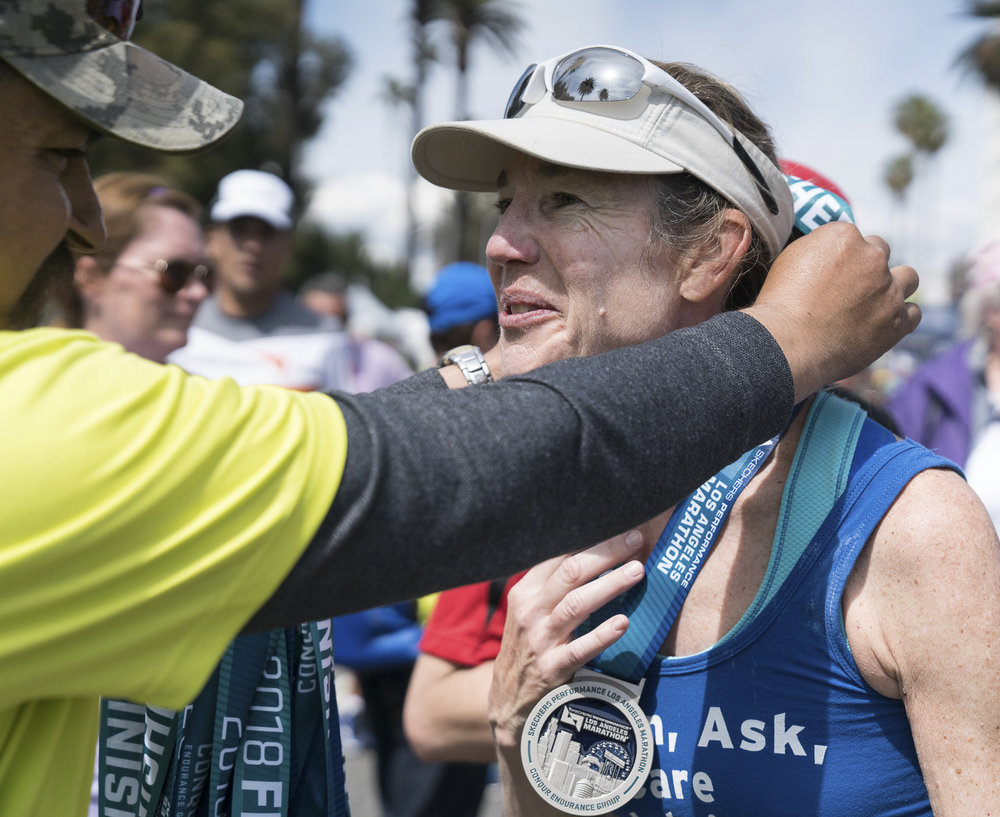 Kathy Welch, who ran the Los Angeles Marathon in memory of her son, SMC student David Sliff, receives her medal in Santa Monica, California on Sunday, March 18, 2018. This was Kathy's 13th marathon, but the first she ran in memory of her son, who died by suicide on December 30, 2017. (Photo by: Helena Sung).