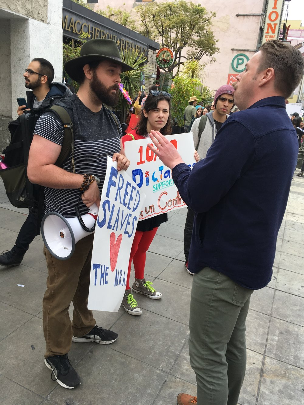Santa Monica College student Ben Kolodny (left), with girlfriend Liberty Fuchs, debating with Spencer Thun about gun control. Kolodny didn't join the corner of counter-protestors at the March For Our Lives protest on March 24, 2018, in Los Angeles, California. Julie Dole/Corsair Contributor Photo).