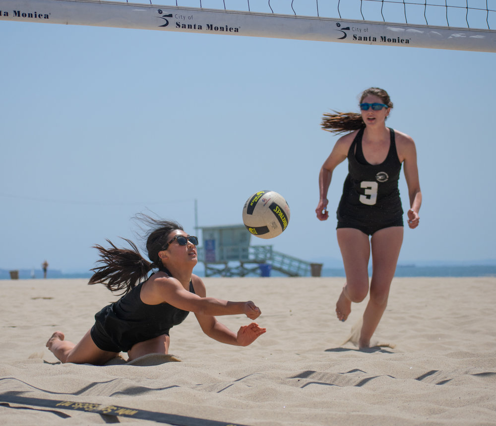 Santa Monica College Corsair Megan Yoon (#11) dives for the ball as partner Chelsea Bostwick (#13) follows during a conference game of beach volleyball in court one against the Bakersfield College Knights at the Santa Monica beach on Friday, April 13, 2018 in Santa Monica, California. It was a 5-0 loss for the Corsairs, bringing their total to 2-12 for the season. (Ethan Lauren/Corsair Photo)