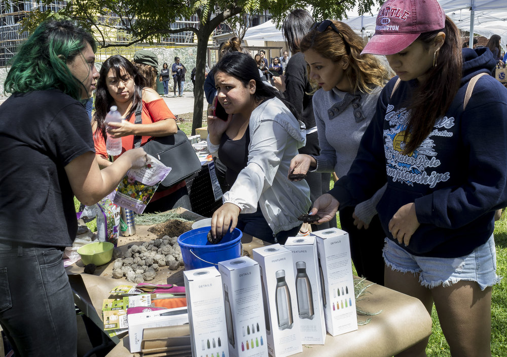 Seed Bombs stand, held by Alexa Benavente (left), freshly elected AS board member for Student Advocacy. Benavente teaches students to make mud balls to plant seeds. Earth Week started with 'Students Feeding Students' Free Farmers Market & Food Demos on Monday, April 16, 2018. At Santa Monica College, Santa Monica California. (Emeline Moquillon/Corsair Photo)