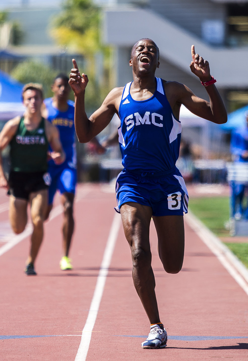 Santa Monica College (SMC) student athlete Cesar Gatete points to the sky with happiness after coming in first place in the men's 800 meter  event during the Track and Field Western State Championships at the SMC Corsair Stadium in Santa Monica California on Friday April 20 2018. (Matthew Martin/Corsair)