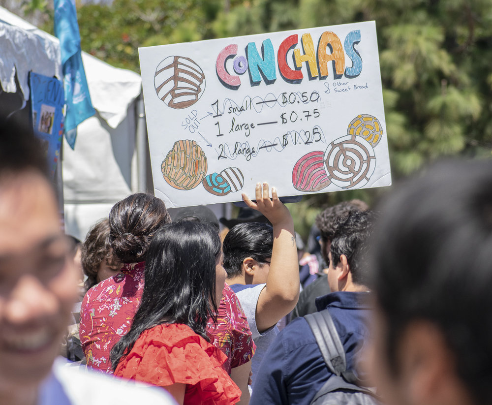 On the quad at Santa Monica College, the Adelante Club advertises the sale of conchas during Club Row on Thursday, April 26, 2018 in Santa Monica, California. With over 60 clubs in attendance, the day is meant to encourage clubs to showcase what they've been doing over the semester for students. (Ethan Lauren/Corsair Photo)