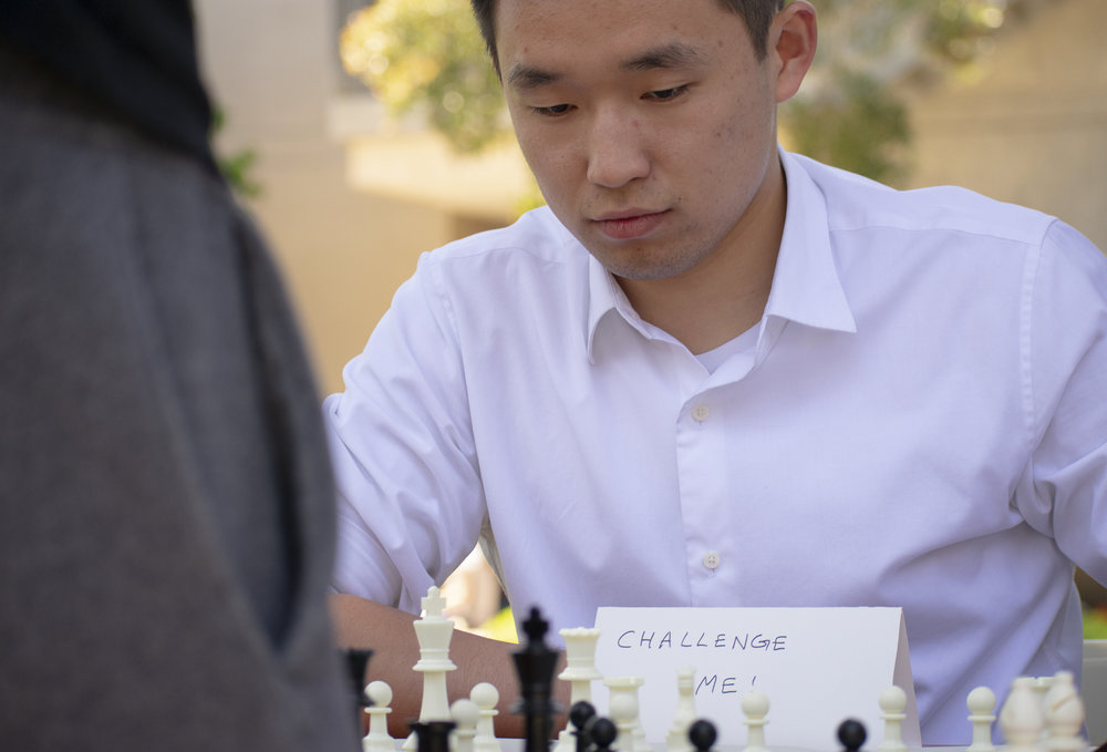 Enkhtuvshin Doyodkhuu, the president of the Chess Club, plays a game with a passerby on the quad at Santa Monica College during Club Row on Thursday, April 26, 2018 in Santa Monica, California. With over 60 clubs in attendance, the day is meant to encourage clubs to showcase what they've been doing over the semester for students. (Ethan Lauren/Corsair Photo)