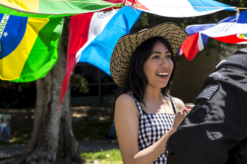 """Santa Monica College (SMC) student and """"Adelante"""" Club member Lesley Calvo interacts with students passing by the Cinco De Mayo celebration event that took place in front of the clock tower on the SMC main campus in Santa Monica California on Thursday, May 3 2018. This event was put together by the Santa Monica College club """"Adelante,"""" whose goal at the event was to inform students about the origins of Cinco De Mayo and put to rest the stereotypes that come with the holiday, specifically the misperception that it is a day of independence for Mexico and also that is just a drinking holiday in the United States. (Matthew Martin/Corsair Photo)"""