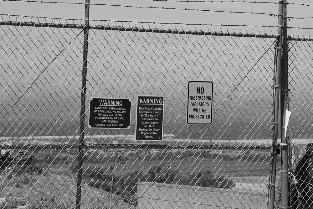 A barbed fence lined with cameras end the pristine street that overlooks LA and the SoCalGas storage facilty in Playa del Rey. Here the signs state that the chemicals beyond the fence are harmful to human life, however the facility is still in eye view on Saturday, May 5, 2018. (Pyper Witt/ the Corsair)