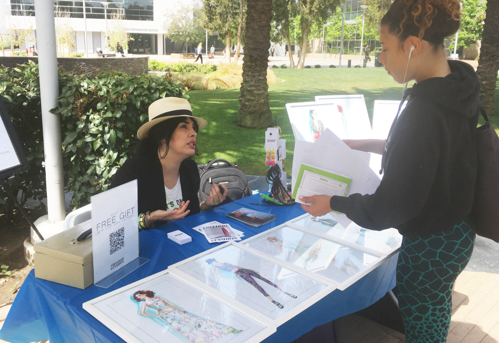 Laverne Delgado-Small explains Freedom Fashion's job opportunities to SMC business student ChaCha at the Spring 2018 job fair. (Julie Dole/Corsair Photo)