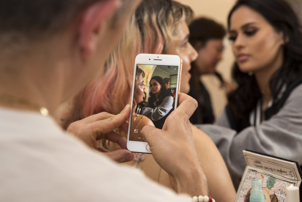 "Instagram influencer Jared Bailey (left) records Amy Woodfine (middle) get her makeup done for her by makeup tutorialist and Instagram influencer Christen Dominique (right) before the LGBTQ+ Prom that is being held at the interfaith Church in Ocean Park in Santa Monica California on Friday May 18, 2018. The interfaith church has held ""Queer Proms"" in the past, but this year was the first that the prom's sponsor, Young People Creating Change (YPCC), partnered with the Princess Project Los Angeles (PPLA), Benefit Cosmetics, and Teen Vogue to produce the event. (Matthew Martin/Corsair Photo)"