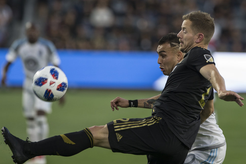 Los Angeles Football Club (LAFC) member Jordan Harvey (front) keeps the ball away from Minnesota United Football Club (MUFC) midfielder Miguel Ibarra (back) during their match at Banc of California Stadium on May 9, 2018 where the LAFC won 2-0. (Zane Meyer-Thornton/Corsair Photo)