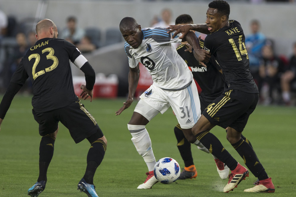 Minnesota United Football Club (MUFC) midfielder Maximiniano (31, middle) battles for control of the ball against Los Angeles Football Club members Laurent Ciman (23, left) and Mark-Anthony Kaye (14, right) during their match at Banc of California Stadium on May 9, 2018 where the LAFC won 2-0. (Zane Meyer-Thornton/Corsair Photo)