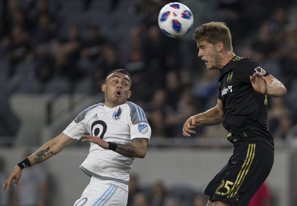 Los Angeles Football Club (LAFC) defender Walker Zimmerman (25, right) headers the ball away from Minnesota United Football Club (MUFC) midfileder Miguel Ibarra (10, left) during their match at Banc of California Stadium on May 9, 2018 where the LAFC won 2-0. (Zane Meyer-Thornton/Corsair Photo)