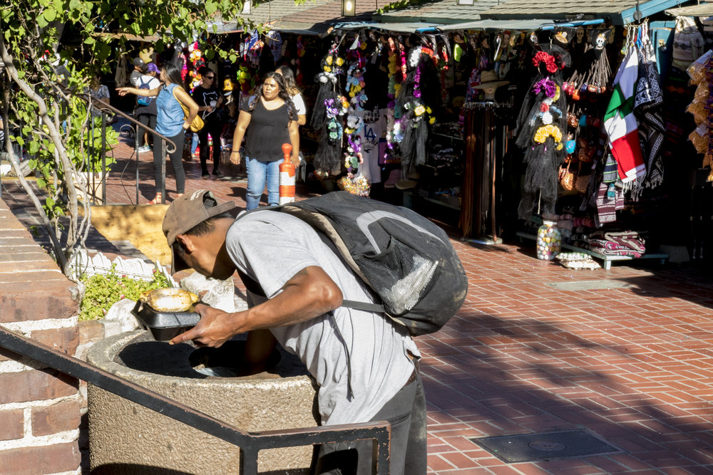 A homeless man digs through a garbage can on Olvera Street as people walk by on October 31, 2018 in downtown Los Angeles, California. (Zane Meyer-Thornton/Corsair Photo)