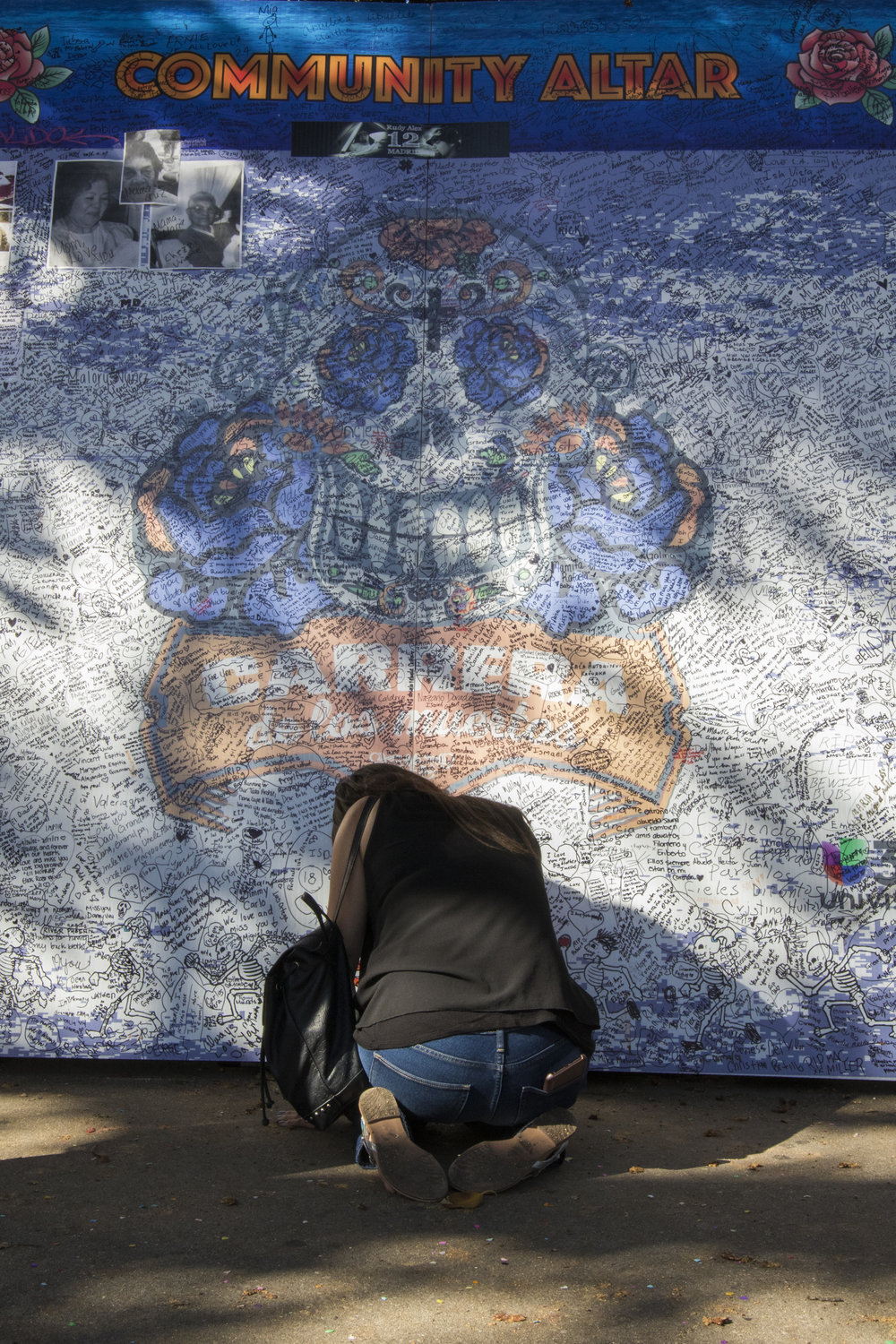 A woman pays respect for her deceased loved one at the Community Altar as part of the Dia De Los Muertos festivities on Olvera Street in downtown Los Angeles, California. The community altar is a place where event attendees can write the name or leave a photo of someone close to them who has passed away. (Zane Meyer-Thornton/Corsair Photo)