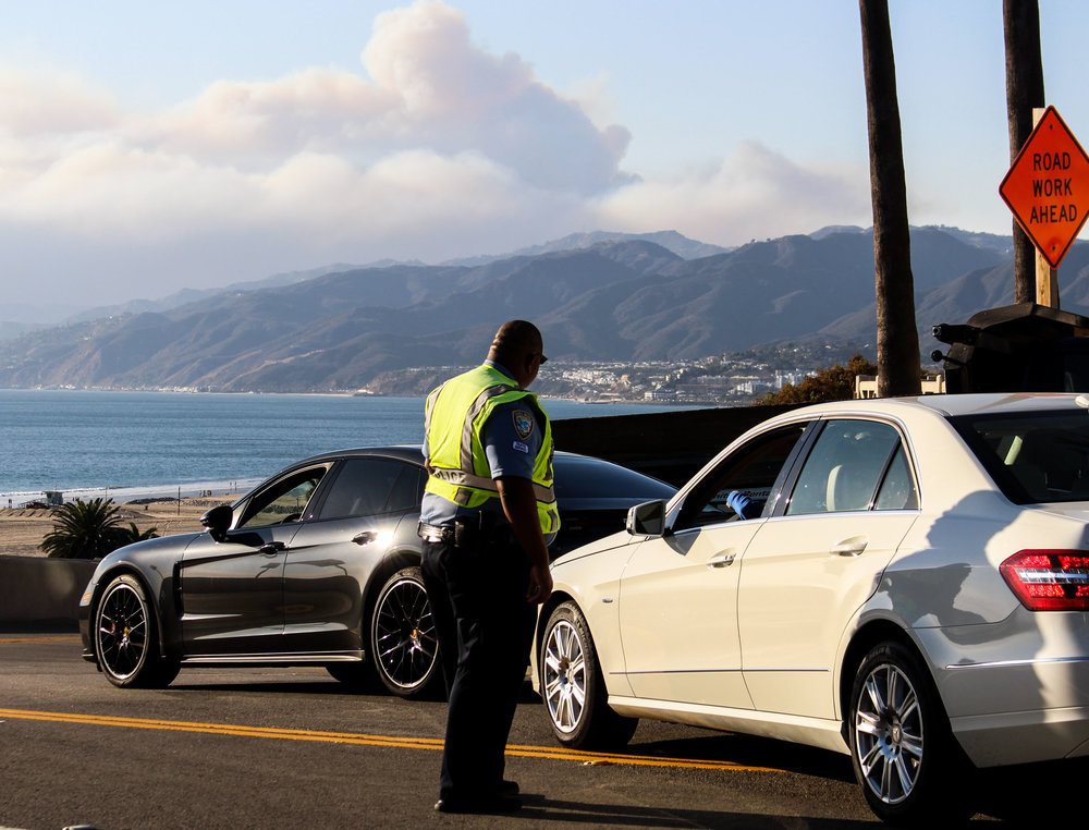 Santa Monica Police officer stands by as Malibu residents attempt to drive through the closed off California Incline off of Ocean Ave in Santa Monica, California, on November 9, 2018. (Pyper Witt/ Corsair Staff)