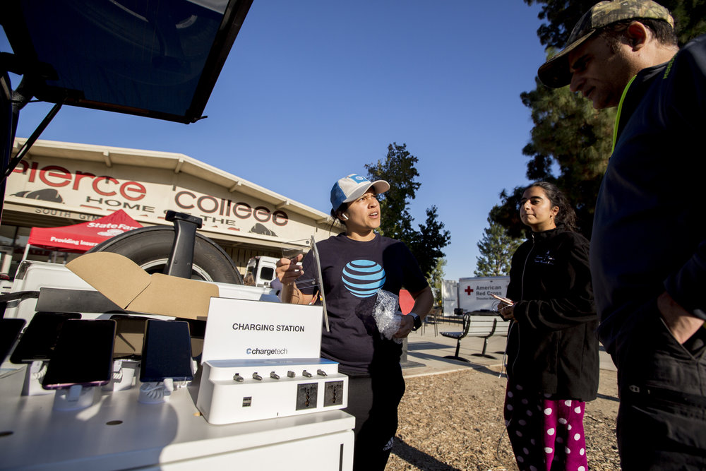 Crystal Segura, with ATT, speaks with evacuees inviting them to charge their phones at the charging station that she is setting up at the Woolsey fire evacuation center at Los Angeles Pierce College on November 9, 2018 in Woodland Hills, Calif. (Jose Lopez)