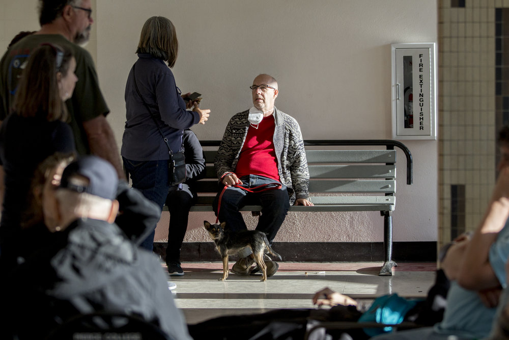 """Scott Geske (center), from Oak Park, sits with his family and dog, Jasper, at the Woolsey fire evacuation center set up at Los Angeles Pierce College on November 9, 2018 in Woodland Hills, Calif. Geske reflected on how they moved into the neighborhood about 14 years ago during the summer and months later in September they experienced their first fire leading him to wonder, """"What kind of decision did we make here?"""" He went on to say that this fire is much worse than the fire that hit the area when they first moved in due to the stronger wind conditions today, which gave his family less time to evacuate this time around. Geske has been told that his house still stands at this point but that he knows people who were not so lucky and who have lost their homes. (Jose Lopez)"""