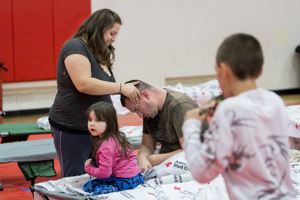 An evacuee cares for her husband and family at the Woolsey fire evacuation center set up at Los Angeles Pierce College on November 9, 2018 in Woodland Hills, Calif. (Jose Lopez)