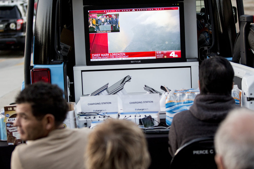 Evacuees watch the news at the charging station outside the Woolsey fire evacuation center set up at Los Angeles Pierce College on November 9, 2018 in Woodland Hills, Calif. (Jose Lopez)