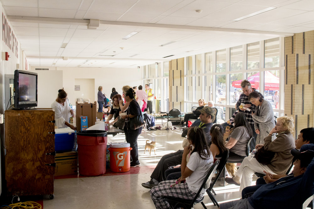 Evacuees of the Woolsey Fire watch live news to get updates on their homes and neighborhoods and receive nourishment at their evacuation center located at Pierce College in Woodland Hills, California on November 9, 2018 (Zane Meyer-Thornton/Corsair Photo)
