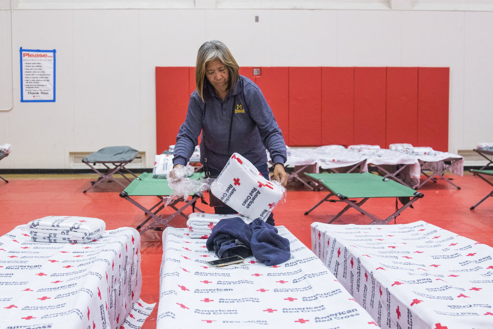 Irene Geske sets up cots for her family inside of Pierce Colleges North Gym in Woodland Hills, California on November 9, 2018. Irene and her family evacuated their home in Oak Park, California two nights ago, but spent last night at a hotel in Van Nuys, California because it was the only place who would allow access to their dog. (Zane Meyer-Thornton/Corsair Photo)