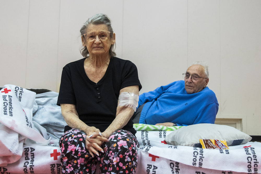 Penny Stark (left) and Ron Stark (right) relax at an evacuation center located at Pierce College in Woodland Hills, California on November 9, 2018 after evacuating their home in Oak Park, California the night before. The started their evacuation with a trip to Kaiser Permanente to get treatment for a pre existing medical condition that Penny has. The couple has lived in Oak Park for the last 50 years and have been evacuated from their home 3 times due to fires, but they refuse to move, because it is their home and they love it. (Zane Meyer-Thornton/Corsair Photo)