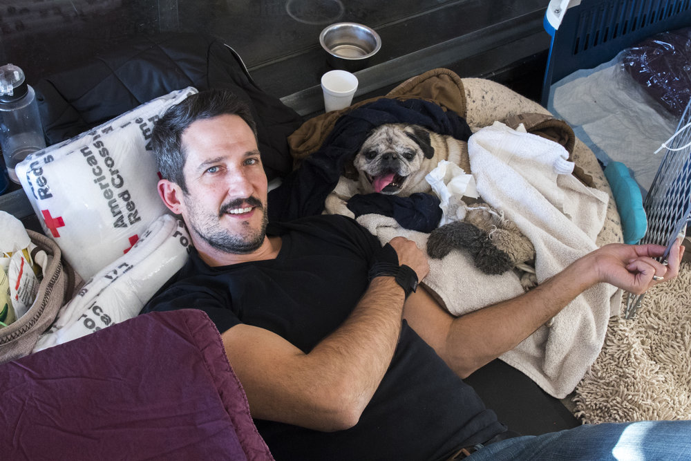 Tony D'Amore relaxes with his paralyzed dog, Bogey at an evacuatin center located at Pierce College in Woodland Hills, California on November 9, 2018. Tony said that since Bogey cannot move around due to his paralyzation, he was very happy to be at the evacuation center because someone laid around with him all day. (Zane Meyer-Thornton/Corsair Photo)