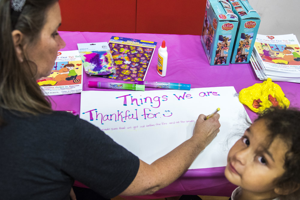 Kiara Baker (6, right) and her grandmother Alicia Koslov (left) make a list of things they are thankful for after taking refuge in Pierce Colleges North Gym in Woodland Hills, California on November 9, 2018. The family was able to have a swift evacuation because they had a motor home packed with supplies for a weekend camping trip, before finding out they had to evacuate their home. (Zane Meyer-Thornton/Corsair Photo)