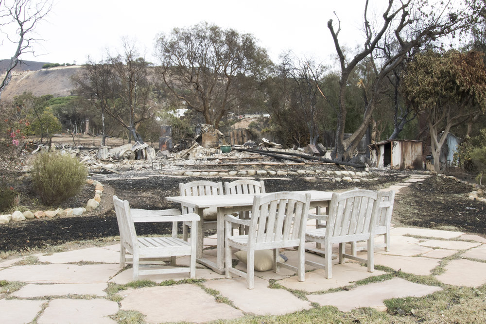 An outdoor table sits unharmed in front of the remnants of a house burned to the ground by the Woolsey Fire in Malibu, California on November 13, 2018 (Zane Meyer-Thornton/Corsair Photo)