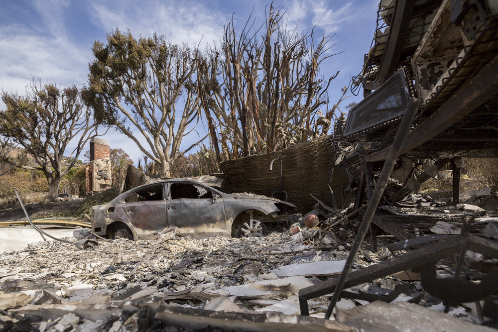 A car devoured by the Woolsey fire sits in the ashes of a garage along Harvester Road on November 14, 2018 in Malibu, Calif. (Jose Lopez)
