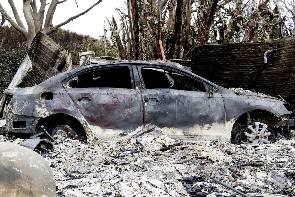 A burned car sits in the driveway of the remnants of a house burned to the ground by the Woolsey Fire in Malibu, California on November 13, 2018 (Zane Meyer-Thornton/Corsair Photo)