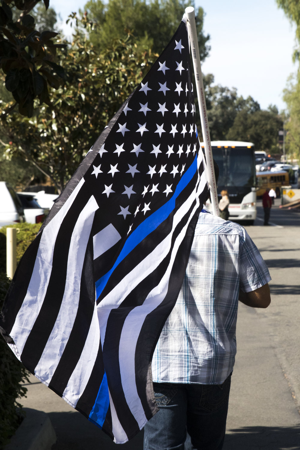 A man carries a Thing Blue Line Flag to represent support for law enforcement officers at the Calvary Community Church in Westlake Village, California on November 15, 2018. (Zane Meyer-Thornton/Corsair Photo)
