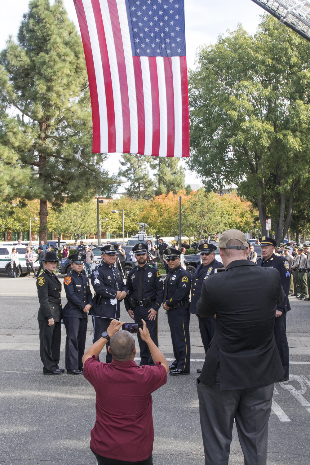 Law Enforcement Officers from Los Angeles Police Department, Dallas Police Department, and New York Police Department pose for a photo in front of an American Flag at the Calvary Community Church in Westlake Village, California on November 15, 2018. (Zane Meyer-Thornton/Corsair Photo)