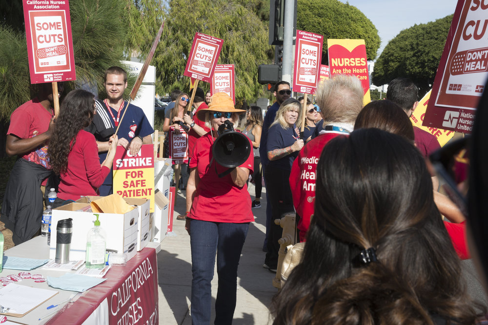 """Sudie Cannone (middle), a registered Nurse and member of the California Nurses Association  chants """"Nurses on the outside, trouble on the inside!"""" at a Nurses Strike outside of Providence Saint Johns Health Center in Santa Monica, California on November 27, 2018. The nurses were striking over the unfair treatment they are receiving from Providence Health and Services. (Zane Meyer-Thornton/Corsair Photo)"""